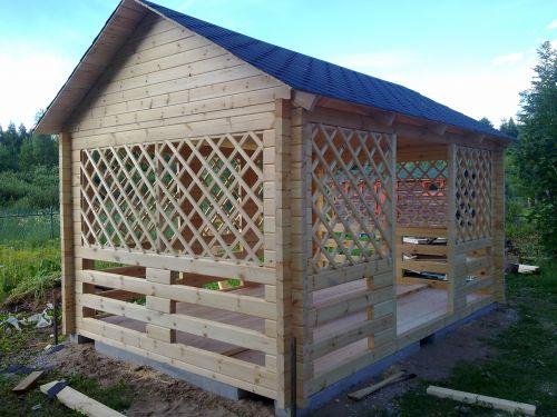 Беседка из профилированного бруса с решетчатым деревянным ограждением и двускатной крышей