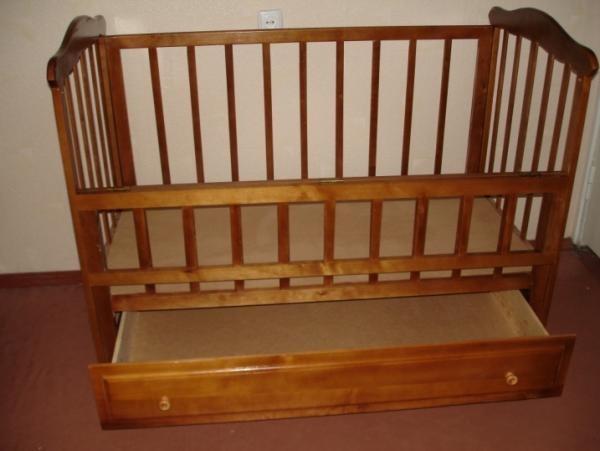 Деревянная детская кроватка с выдвижным ящиком в нижней части