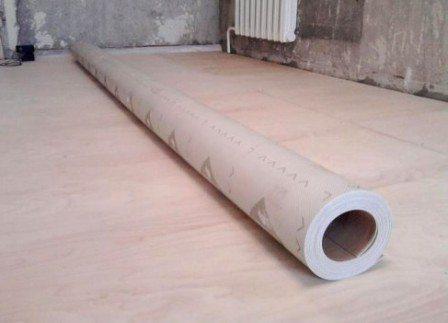 Фото рулона линолеума, готовящегося к укладке на фанерный пол