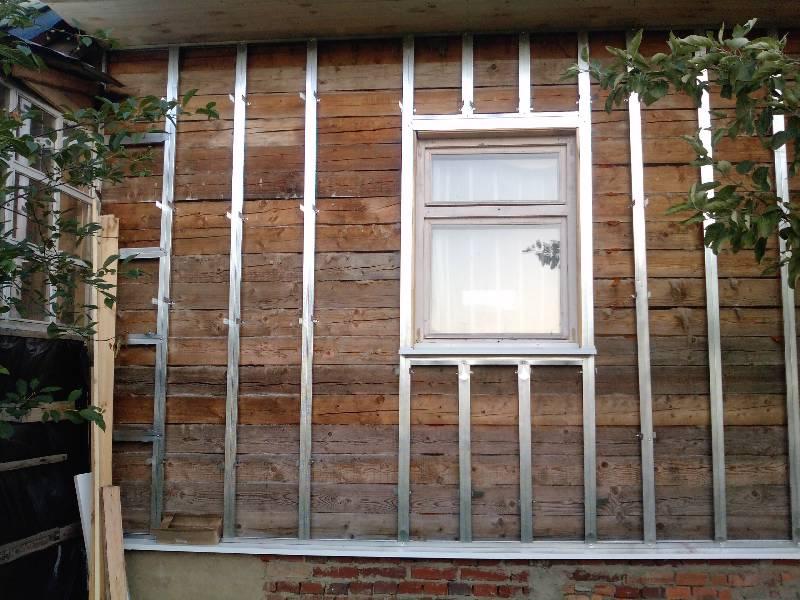 Монтаж металлических направляющих на деревянный фасад.