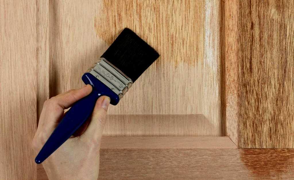 На фото - нанесение пропитки на деревянную дверь