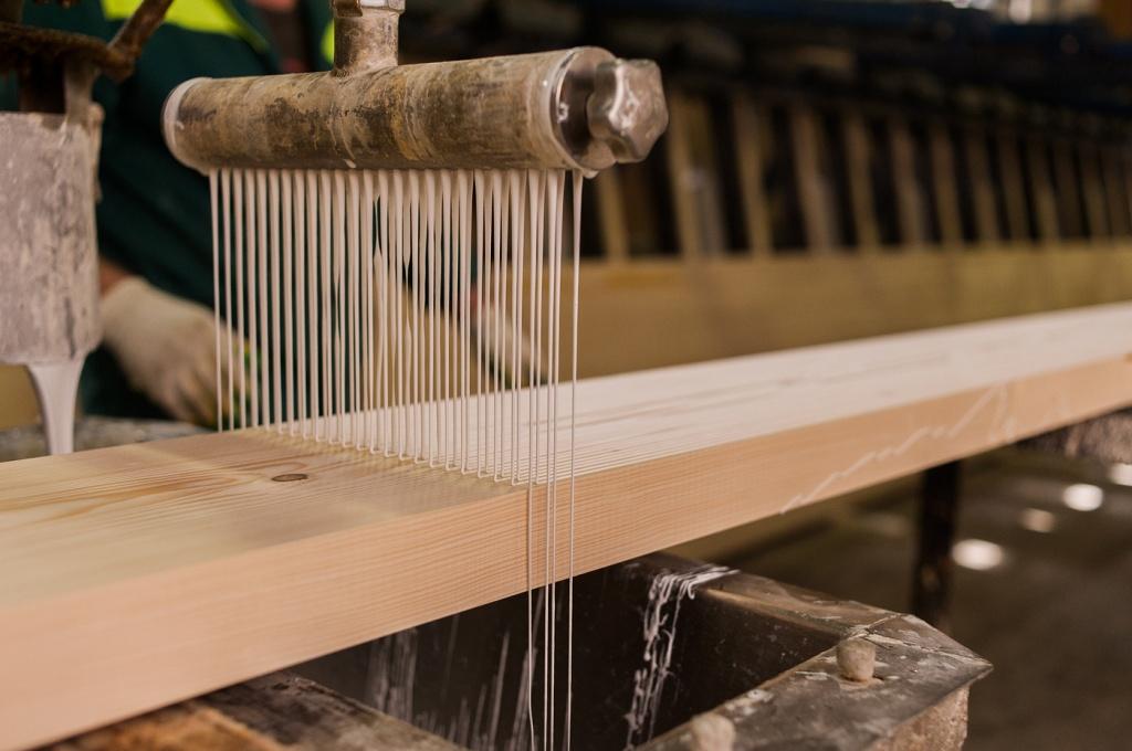 На фото – процесс нанесения клея с помощью специальной машины.