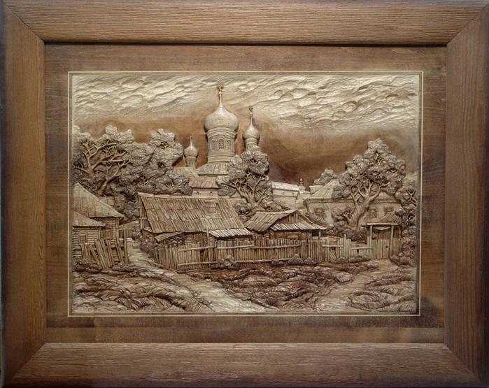 На фото изображено резная картина с видом на деревню.