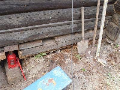 На фото: подъём стены деревянного дома для замены венца