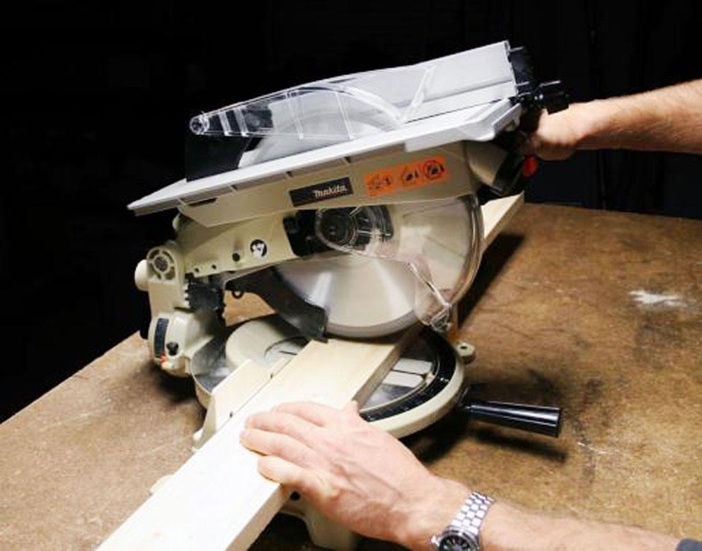 На фото показано правильное положение рук во время распиливания деревянной заготовки.