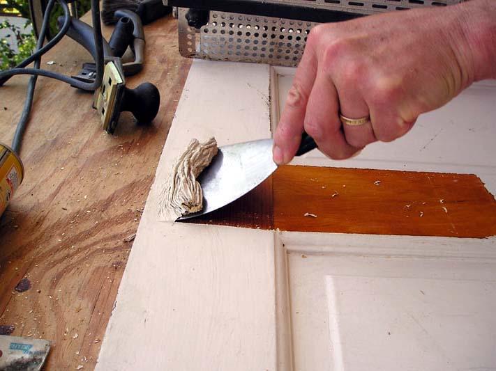 На фото процесс удаления остатков краски с помощью шпателя