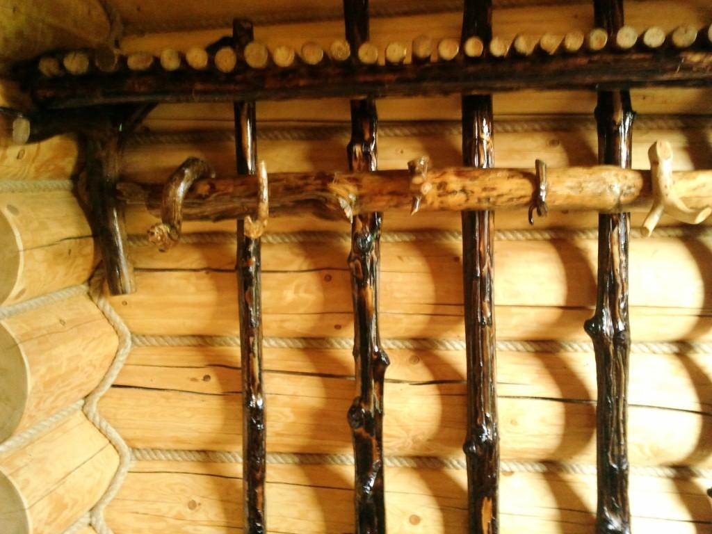 На фото: вешалки в баню из дерева могут изготавливаться из подручных материалов, но искусное окрашивание буквально преображает конструкцию и делает ее очень оригинальной