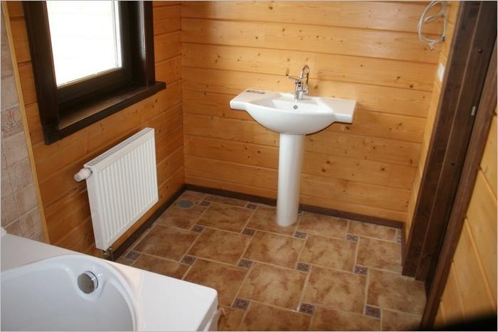 Напольная керамическая плитка в санузле деревянного дома.