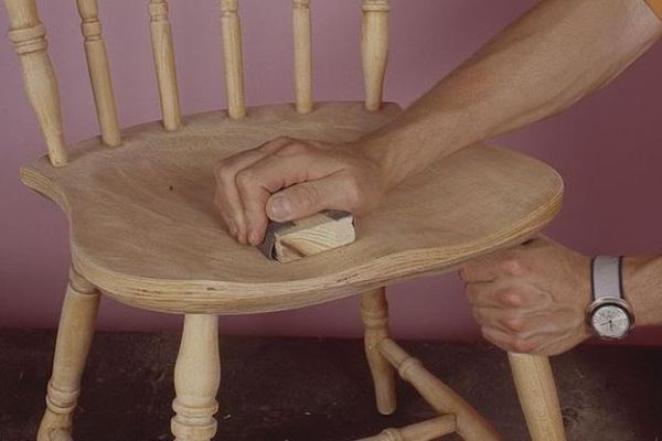Перед тем, как отреставрировать деревянный стул, его поверхность зачищают от лака методом шлифовки.