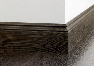 Плинтус из массива ценных пород дерева смотрится великолепно, но и его цена в разы выше обычных вариантов