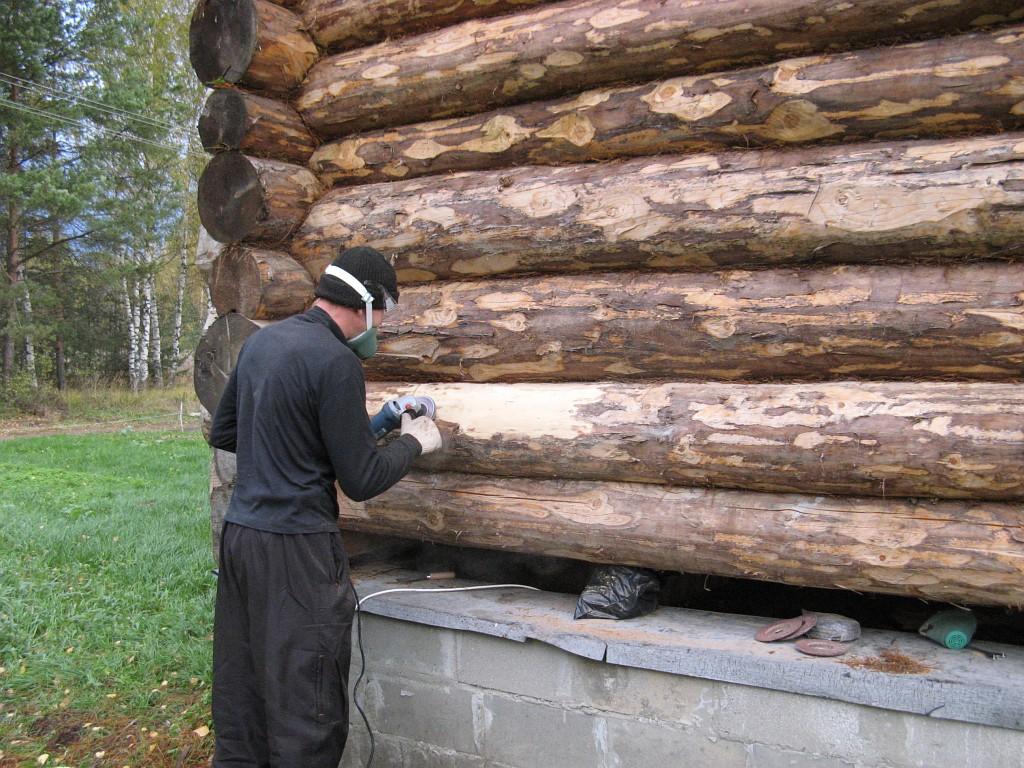 Процедура на фото – удаление остатков коры с поверхности бревен с помощью болгарки