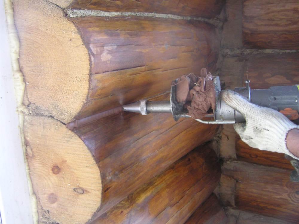 Процесс нанесения состава на межвенцовый шов сруба.