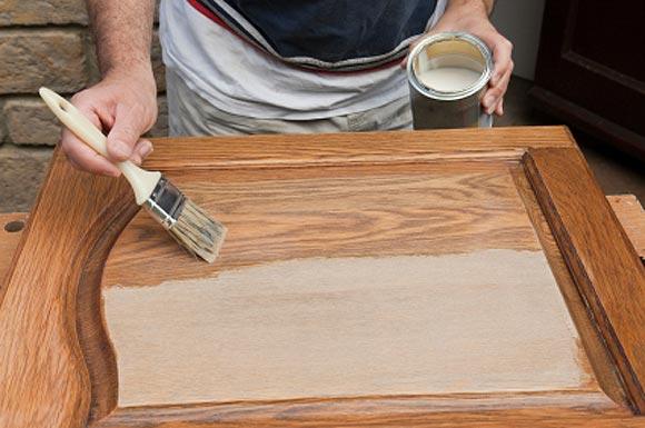 Процесс окрашивания дверного полотна из дерева.