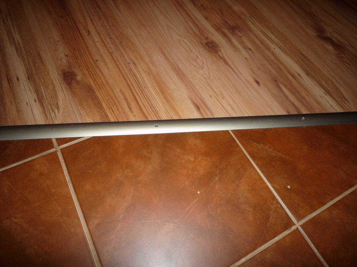 Стык паркетной доски и плитки скрыт алюминиевым порогом.