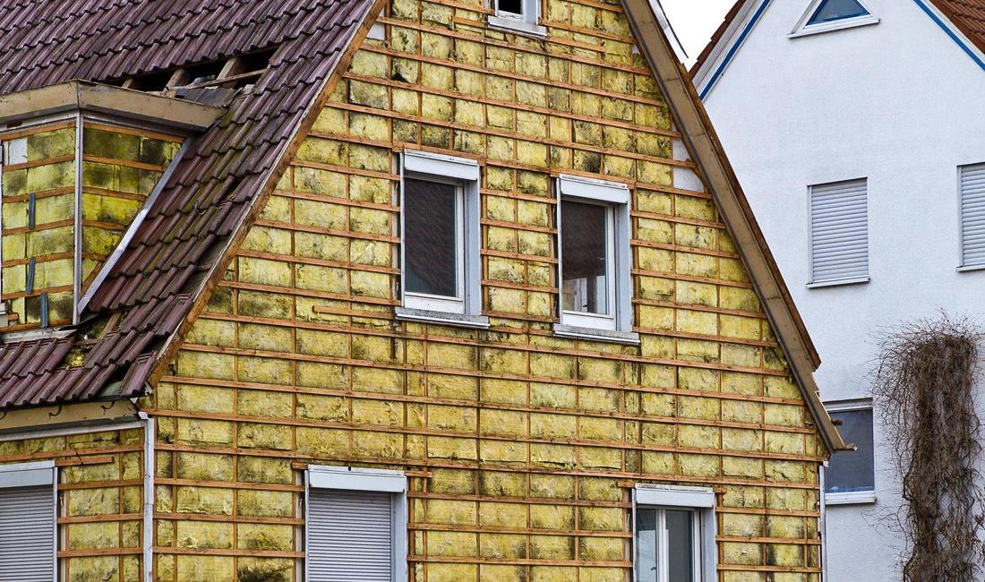 Теплоизоляция фасада двухэтажного дома из дерева.