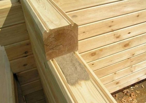 Укладка теплоизоляционного материала между венцами брусового дома