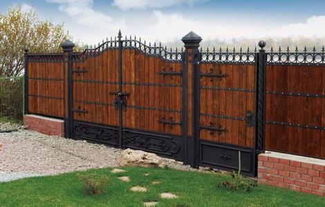 Деревянный забор с ковкой и кирпичным основанием – это не только очень красивое, но и очень прочное сооружение