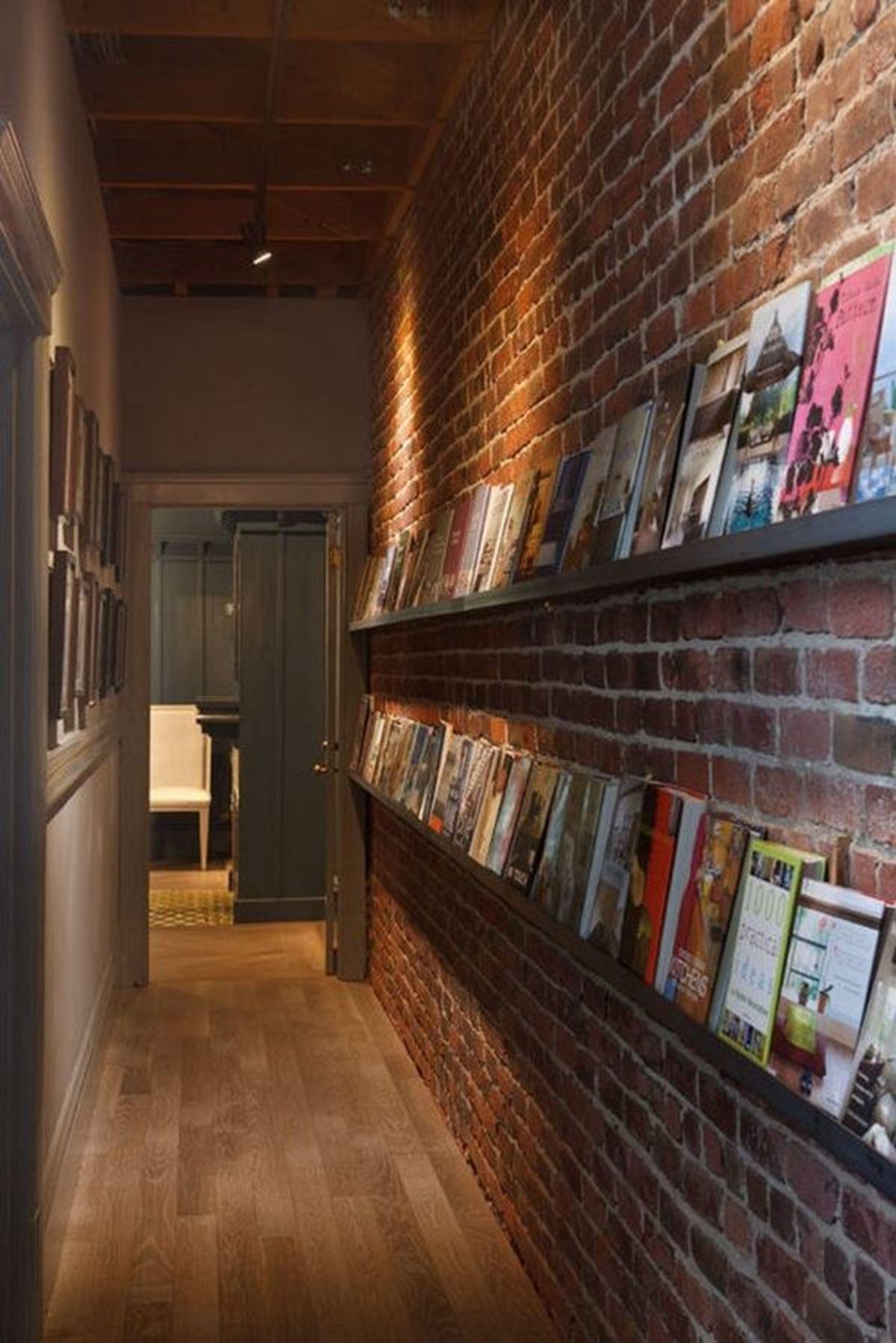 Узкий коридор можно разнообразить с помощью полочек для книг