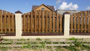 Готовый кирпичный забор с деревянными вставками смотрится очень респектабельно