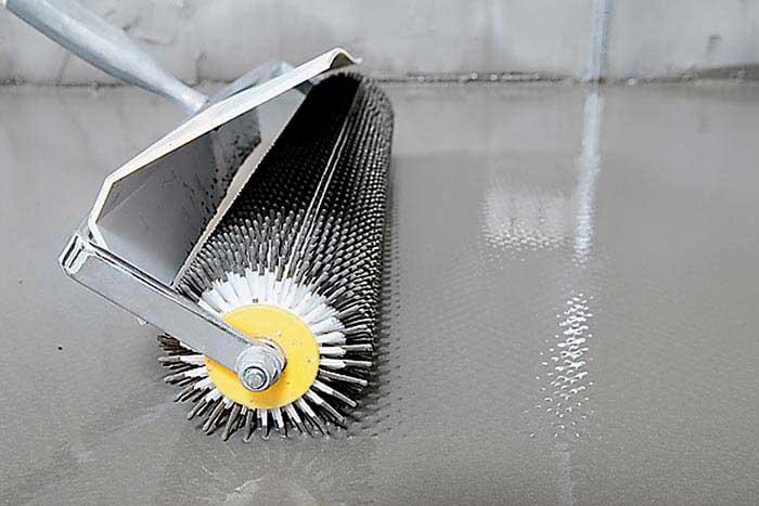 Игольчатый валик поможет разогнать смесь по поверхности пола.