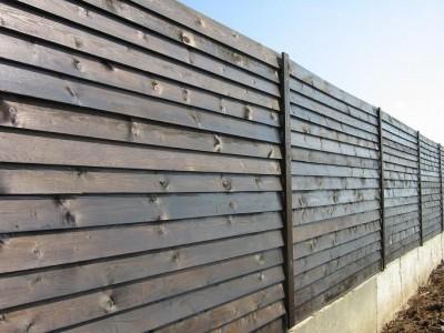 На фото: забор,где монтаж досок выполнен внахлест