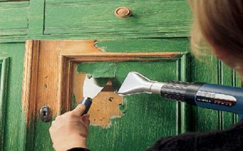 Любительское фото, процесса удаления покрытия с деревянной поверхности при применении строительного фена