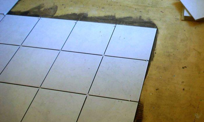 На фото демонстрируется процесс укладки кафеля на фанерную обшивку.