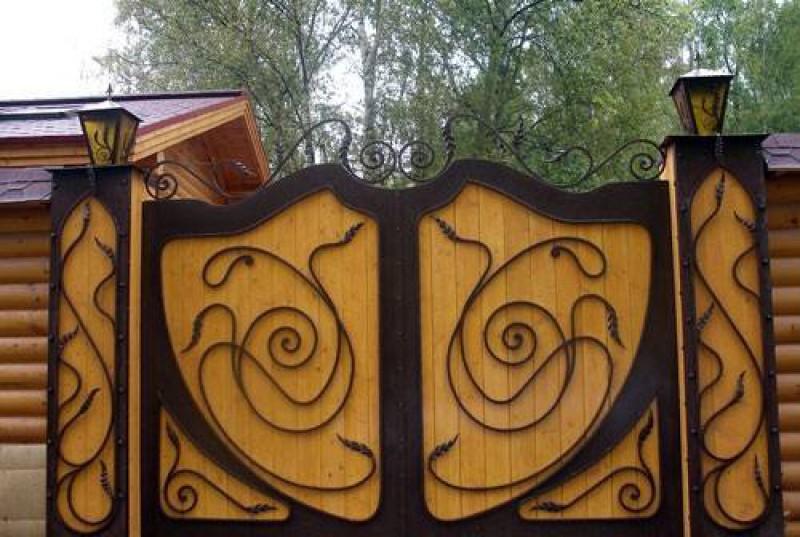 На фото: кованые ворота с деревом могут иметь самый разный дизайн, все зависит от фантазии мастера