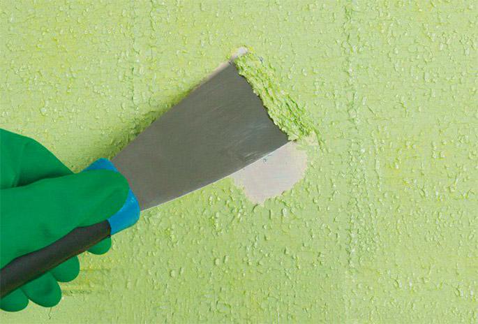 На фото показано удаление размягченной старой краски после применения жидкой смывки.