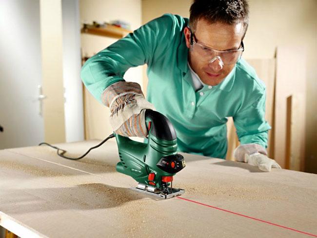 На фото представлен процесс резки древесины при помощи электролобзика.