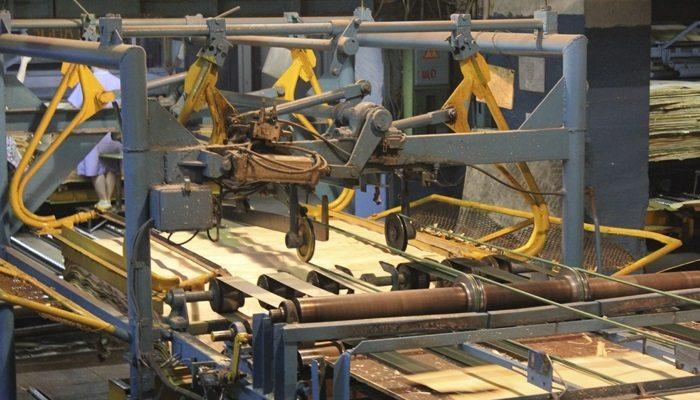 На фото промышленное оборудование для лущения и раскроя шпона