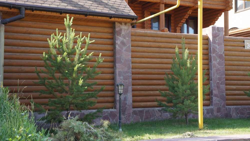На фото запечатлена ограда из оцилиндрованного бревна с каменными столбами.
