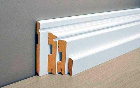 Напольные широкие деревянные белые плинтуса с канавками для укладки проводов