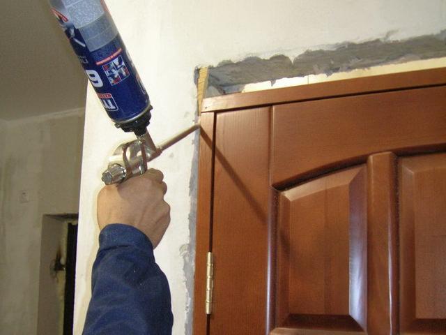 После установки короба с полотном следует с помощью монтажной пены заполнить пустоту между стеной и косяком (как на фото)