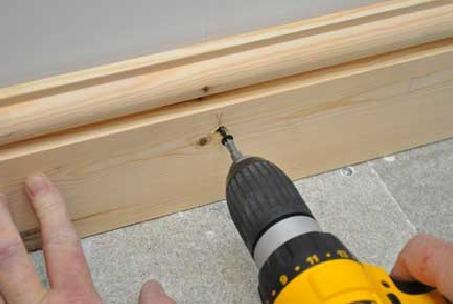 Производится установка плинтуса из массива при помощи саморезов.