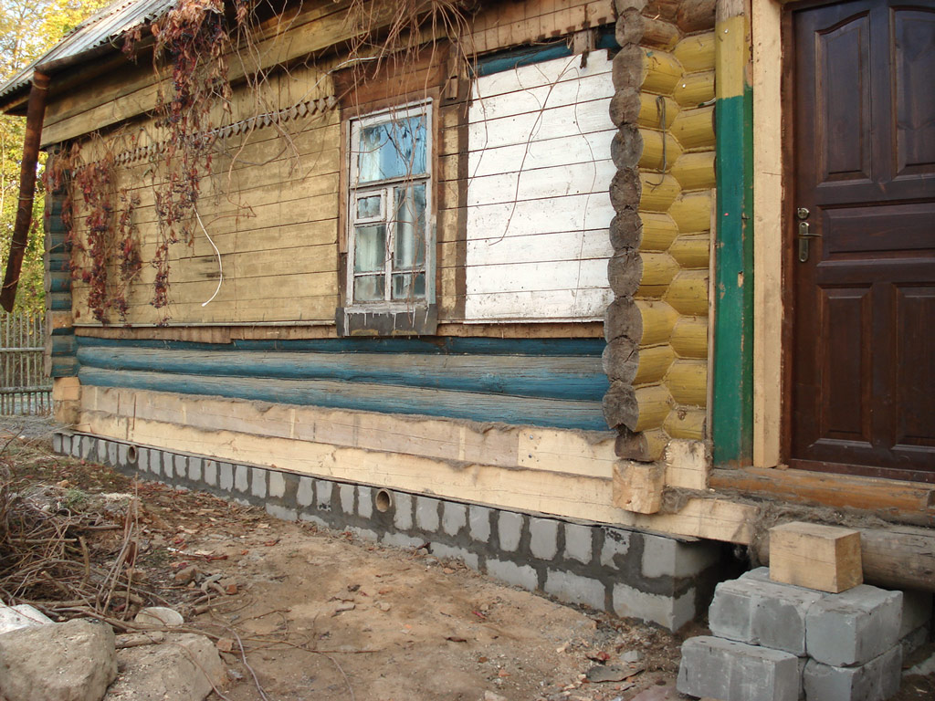 Реконструкция фундамента деревянного дома своими руками часто включает замену бревен нижних венцов.