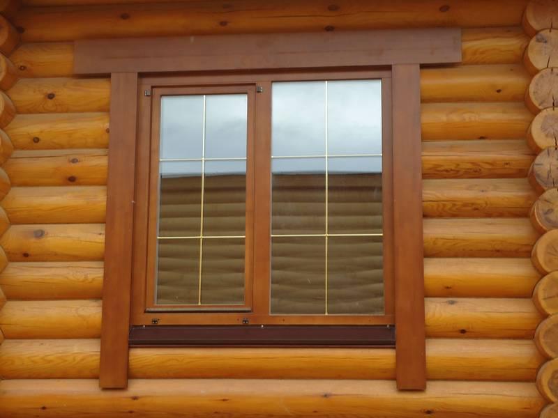 Современные деревянные окна для дачи со стеклопакетом гармонично сочетаются с бревенчатым фасадом.