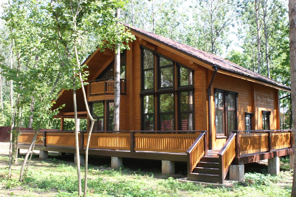 Современные брусовые дома прекрасно сочетаются с окружающими их деревьями