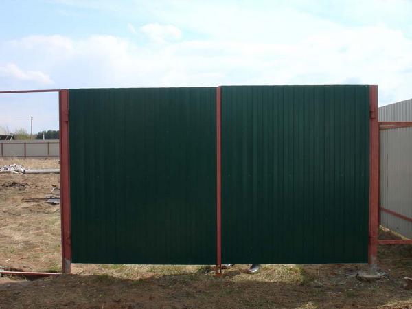 Так выглядят простые самодельные ворота из профнастила на деревянных столбах