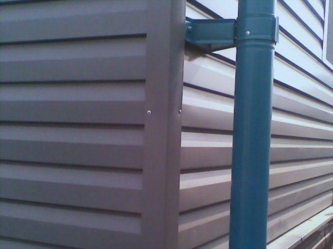 Угол дома, обшитого металлическим сайдингом