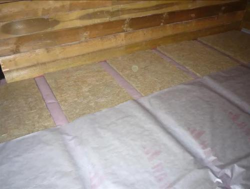 Укладка рулонной гидроизоляции поверх утеплителя в процессе изготовления полов