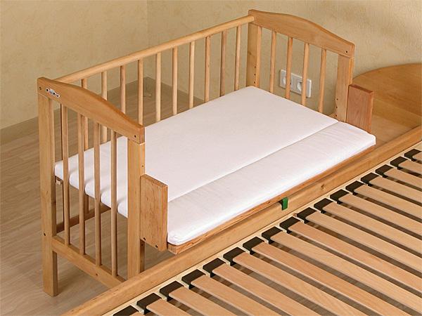 Установка откидного борта позволяет соединять детскую кроватку с родительской