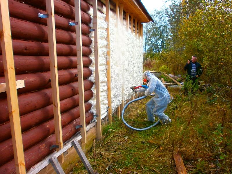 Утепление бревенчатого дома с помощью напыления материала под сайдинг.