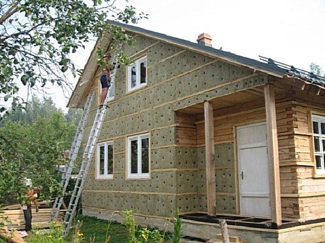 Утепление дачного дома из бруса перед обшивкой сайдингом.
