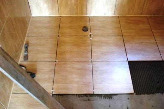 Здесь показано, как укладывается плитка на пол в деревянном доме.